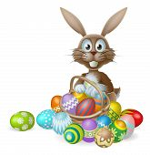 stock photo of ester  - An Easter bunny rabbit with a basket of decorated painted chocolate Easter eggs - JPG