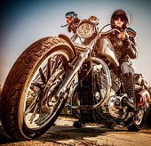 MOSCOW, RUSSIA-JULY 7, 2013: Biker girl on legendary bike Harley Sportster (focus on the wheel).Harley-Davidson sustains a large brand community which keeps active through clubs, events, and a museum.