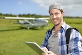 Adventurer using digital tablet in aerodrome