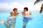 stock photo of infinity pool  - Cheerful couple swimming in infinity pool - JPG