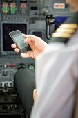 stock photo of cabin crew  - Pilots using smartphone in cockpit of private jet - JPG
