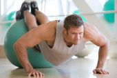 Man Balancing On Swiss Ball At Gym