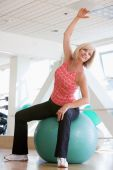 Woman Stretching On Swiss Ball At Gym