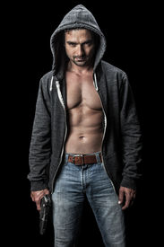 picture of gangsta  - Menacing young man in a hoodie holding a gun - JPG