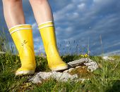 Standing In Yellow Boots Outdoors