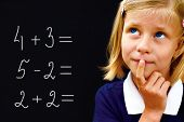 Schoolgirl Doing Arithmetic On Blackboard In Class And Smiling