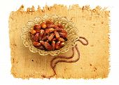 dates in a bowl and islamic rosary image on papyrus paper texture