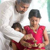 Indian family in traditional dress preparing to celebrate diwali or deepavali at home. Little girl h
