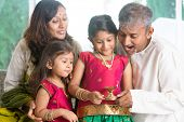 Indian family in traditional sari celebrate diwali or deepavali at home, little girl hands holding o