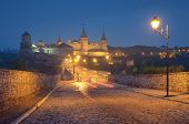 Night landscape with a road leading to the old fortress. Illumination on a historic building. Histor