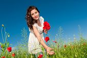 Portrait of beautiful young woman in the field with a poppies bouquet