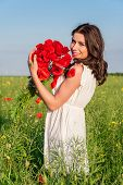 Portrait of beautiful young woman with poppies in the field with a poppies bouquet.