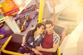 Young smiling couple having a ride on a ferris wheel