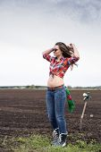 Woman Adjusts Long Hair On Cultivated Field