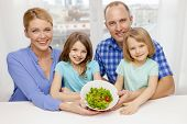 food, family, children, happiness and people concept - happy family with two kids with salad at home