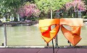 Orange Life Jackets Dried On Fence