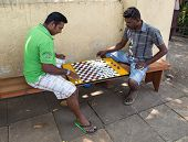 HIKKADUWA, SRI LANKA - FEBRUARY 22, 2014: Local men play checkers on street. Checkers is very popula