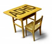 stock photo of fidget  - ADHD Concept for hyperactivity disorder and attention deficit behavior as a school desk with the letters carved into the wooden table as a healthcare symbol for childhood mental health issues - JPG