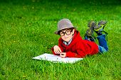 Cute 7 years old boy lying on a grass and reading a book. Summer day.