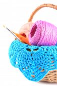 Colorful yarn for knitting with napkin in wicker basket and crochet hook, isolated on white