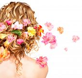 Hairstyle with colorful flowers. Beautiful healthy curly hair decorated with flowers. Isolated on wh