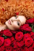 Beauty Fashion Woman with long curly red hair and beautiful red roses bouquet. Hairstyle with flower