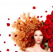 Beauty model woman with long curly red hair and beautiful red roses hairstyle with flowers and petal