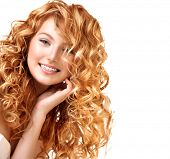 Beauty teenage model girl portrait isolated on white background. Red curly hair. Healthy wavy hair.