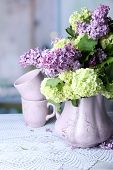 Composition with tea mugs and beautiful spring flowers in vase, on wooden table, on bright background