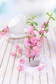 Beautiful fruit blossom in glass on table on light background