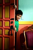 stock photo of sneak  - Photo of a young asian teen peeking and sneaking in into a living room of a house - JPG