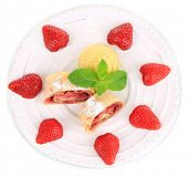 Tasty homemade strudel with ice-cream, fresh strawberry and mint leaves isolated on white