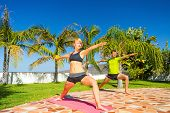 Woman And Man Doing Yoga Outdoors