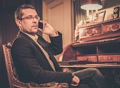 Confident middle-aged man with mobile phone in luxury interior
