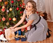 Woman receiving gifts under Christmas tree.