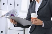 Businesswoman with folders and cup of coffee