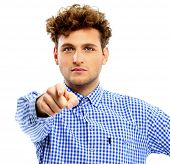 Young man pointing at you over white background
