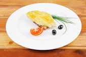 main portion: served roast golden fish fillet over white plate on wooden table with tomatoes and olives