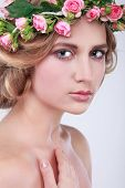 Beautiful young girl with a chaplet from roses   in hairs, emotions, cosmetics, isolated on a light - grey background