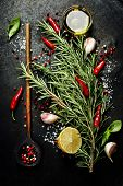 Bunch of spices  and old spoon on dark vintage background. Cooking, vegetarian food or health concept.