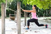 Sport woman doing lunges by the exercise bar in outdoor park