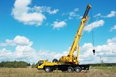 pic of boom-truck  - yellow automobile crane with risen telescopic boom outdoors over blue sky - JPG