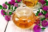Tea with clover in glass teapot on light board