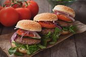 Mini hambugers with tomato and onion on wooden table