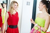 Joyful blond girl in new red dress waiting for her friend opinion in clothing department