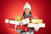 Cheerful young woman in winterwear holding multi-color giftboxes