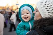Baby boy and his mother outdoors in wintertime