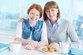 Cute teenage girl and her mother looking at camera with smiles during breakfast