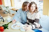 Portrait of amorous dates enjoying sweet dessert and good time in cafe