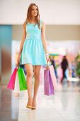 Young female customer with colorful bags visiting mall